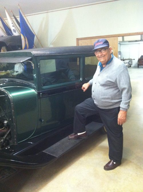 life and death elderly man standing by antique car
